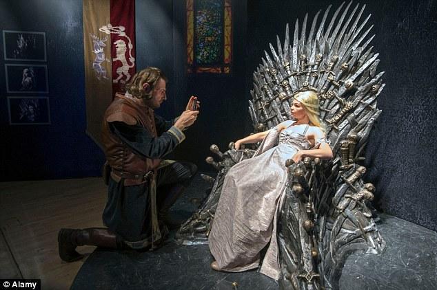 Una fan disfrazada de la reina Daenerys Targaryen, se sienta en el trono de Hierro.